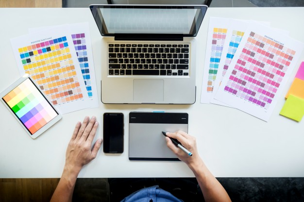 top-view-young-graphic-designer-working-desktop-computer-using-some-color-swatches-top-view_1423-139
